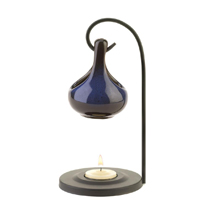 With a generous dollop of charm, this striking oil warmer will mesmerize you with its simple elegance. A metal loop balances the ceramic oil basin above a seated tealight to give off a warm glow and delicate scent.