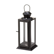 This rectangular candle lantern features a dark metal frame and clear glass panels that allow a candle of your choice to shine brightly. The top of the lantern features a starry cutout pattern and a hanging loop.