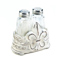 With a fleur-de-lis decoration adorned on the side of this salt and pepper shaker holder, this set is perfect for display on your dining room table. This lovely set offers effortless elegance and elevated appeal to any tabletop.